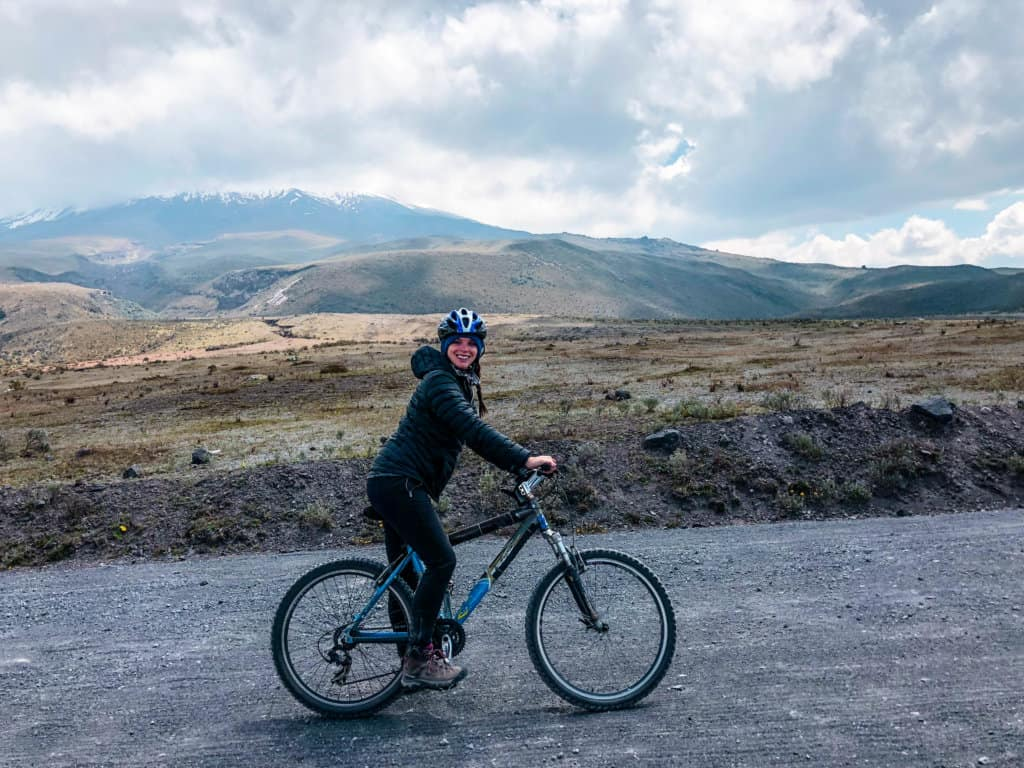 Me on a bike in front of a cloud covered Cotopaxi on my Cotopaxi day trip