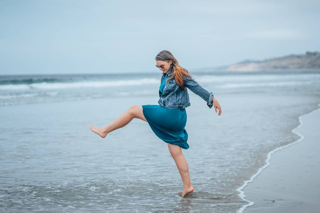 girl kicking leg on beach