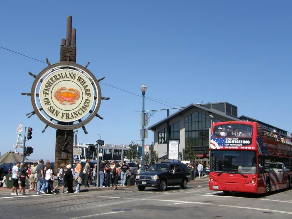 Fisherman's Wharf San Francisco sign with red tour bus