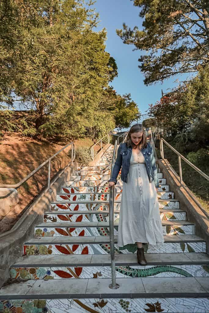 woman in white dress walking down tiled staircase