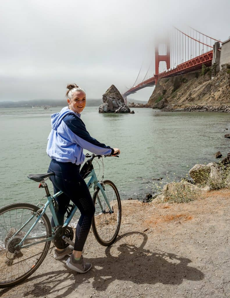 Me on bike looking back at the camera smiling with the Golden Gate Bridge in the background
