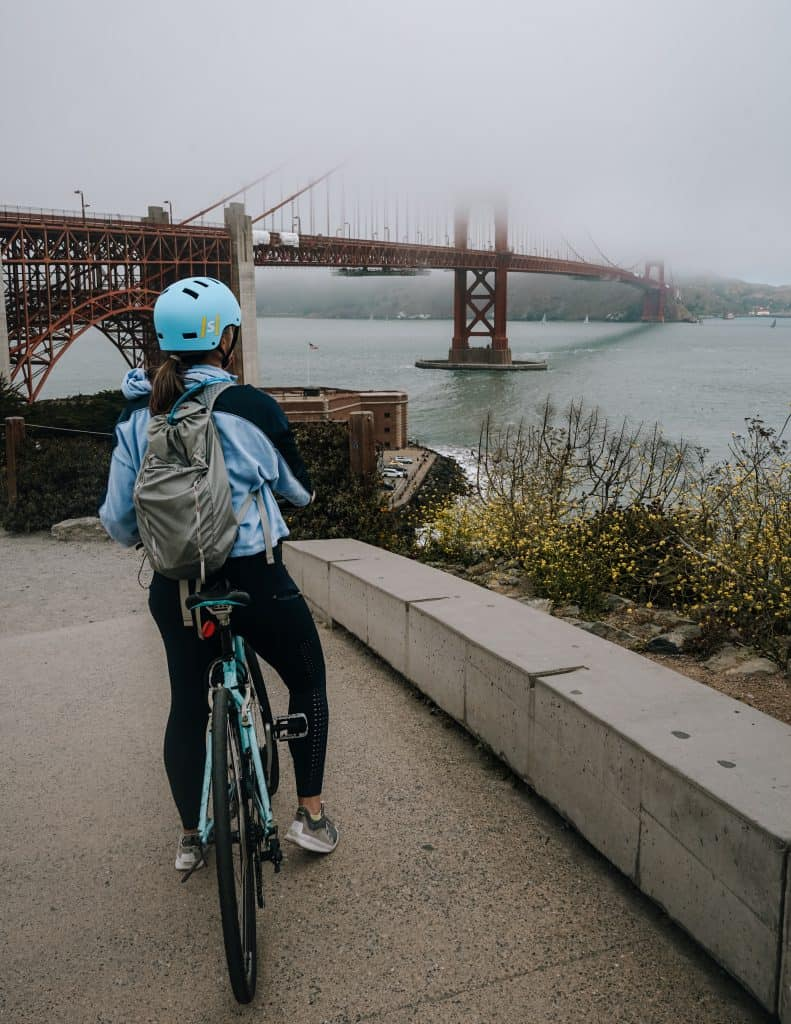 me on a bike looking at the Golden Gate Bridge covered in fog
