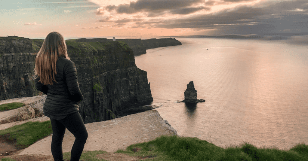 Planning a solo trip? Here's how to decide your destination. Image: Woman overlooking the Cliffs of Moher in Ireland