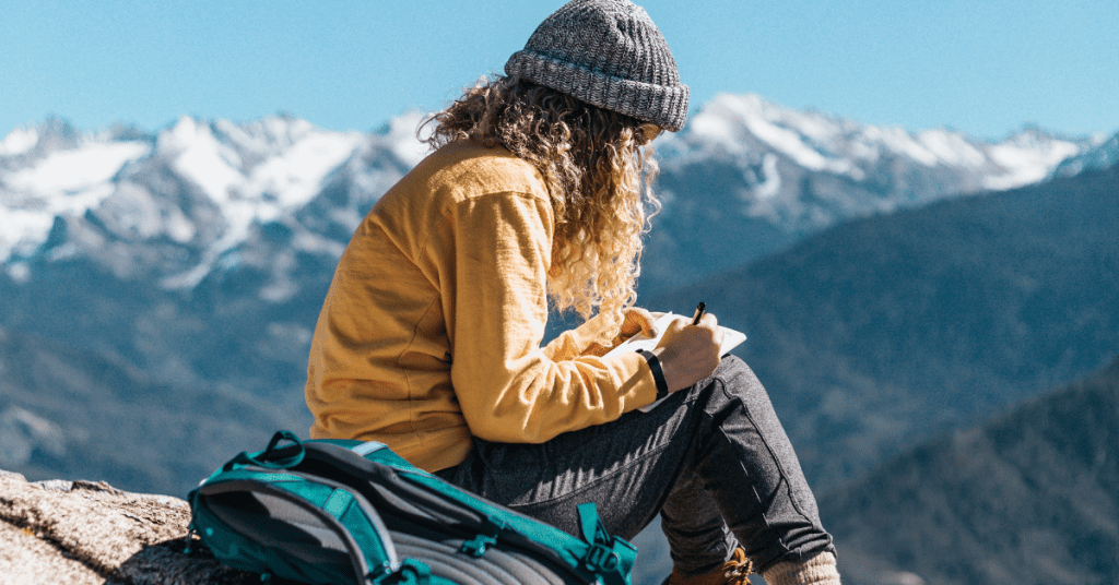 Planning a solo trip requires a solid bucket list. Image of a woman sitting on a mountain top journaling.