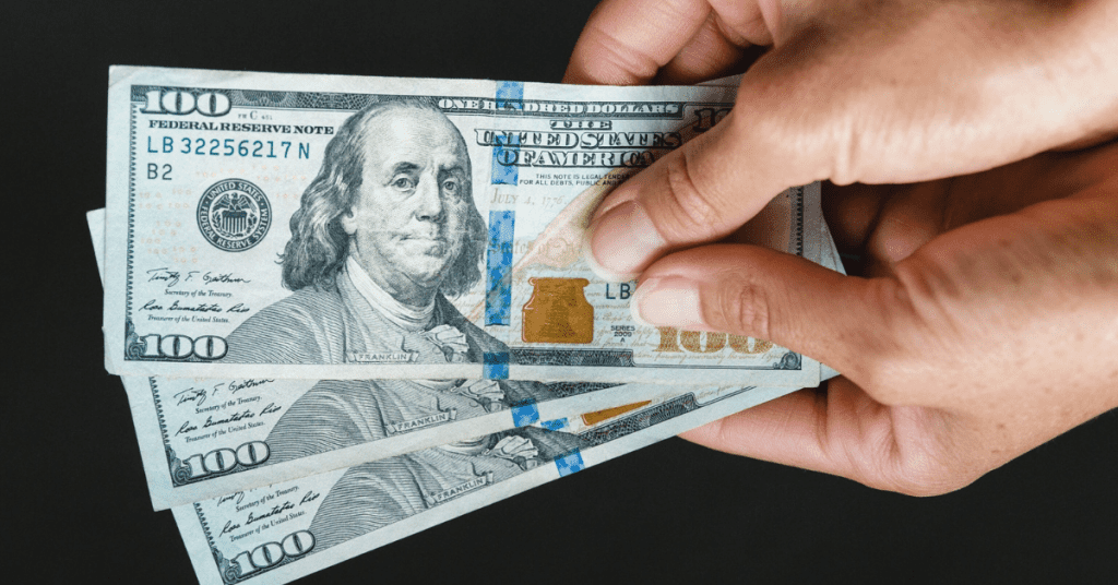 Need to plan a budget friendly solo trip? Here are a few tips! Image of hands holding 3 $100 bills.