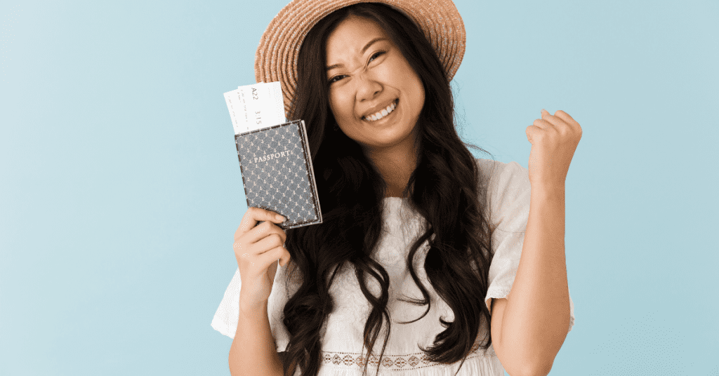 How to plan a solo trip? Make sure you get your Passport and other paperwork in order early. Image of a woman holding a passport and smiiling.