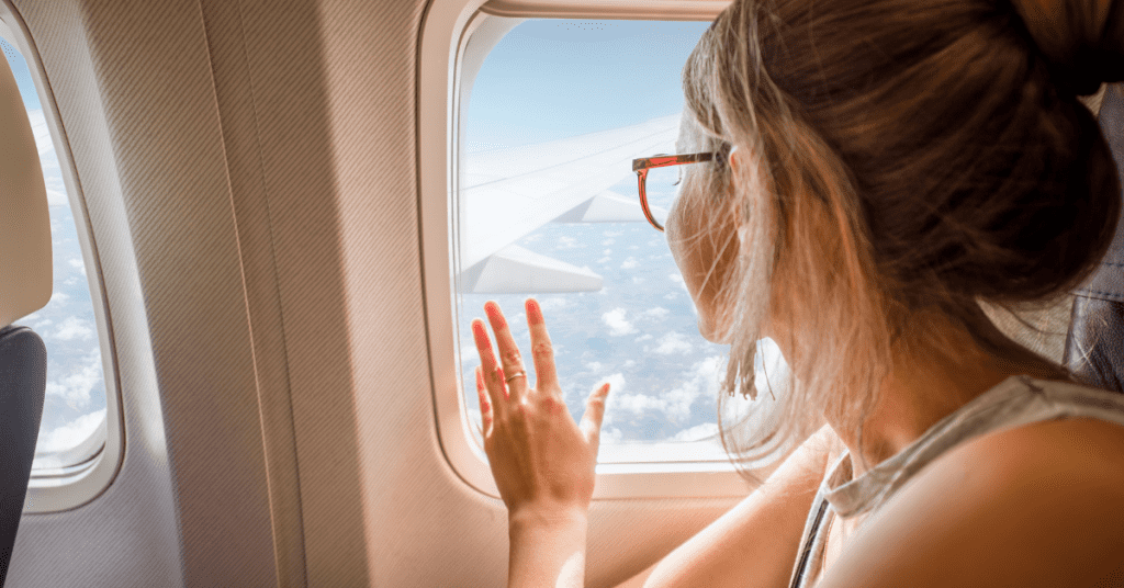 Planning a solo trip? Make sure to book your transportation using these steps! Image of a woman looking out of an airplane window.