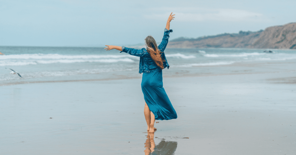 Travel with confidence by purchasing travel insurance before your flight. Image of a woman walking on a beach with her hands in the air.