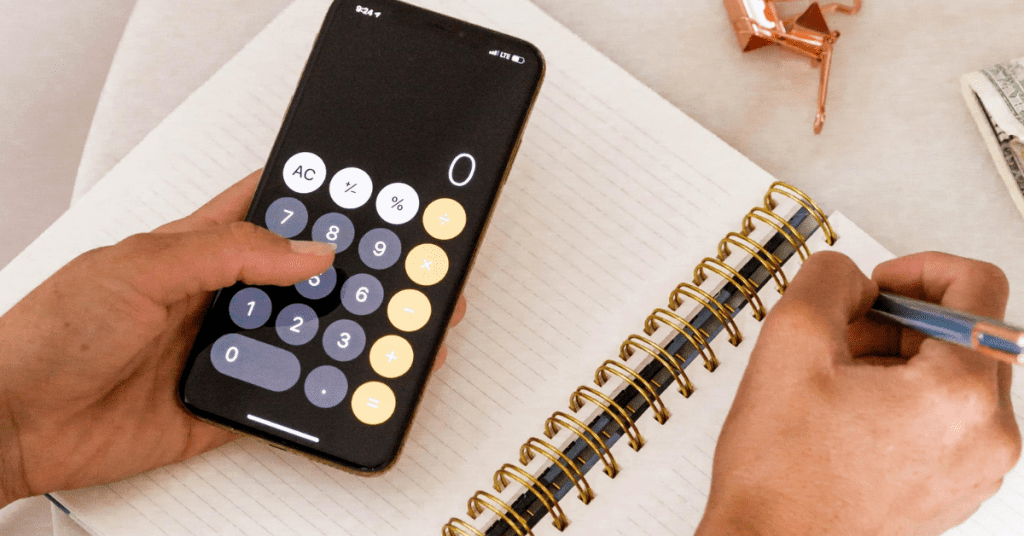 Planning a trip requires having a travel budget. Image of calculator on phone and hand writing in a notebook with a pen.